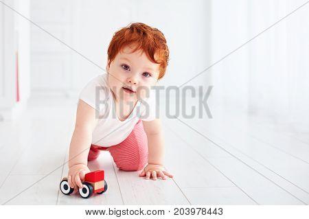 Cute Redhead Baby Boy Rolling A Toy Car On The Floor