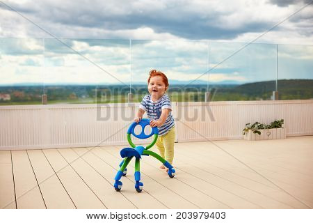 Happy Toddler Baby Boy Pushing Pushing Go Cart, Outdoors