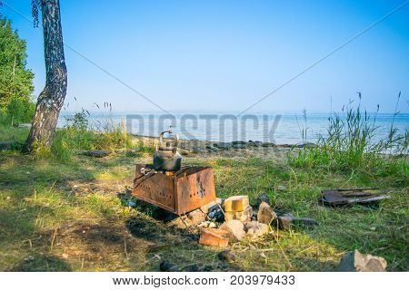 Bloated teakettle on a fire at a bank of a lake - hiking landscape,  Uveldy, The Urals, Russia