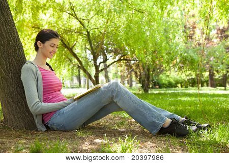 Young Girl Reading Book In Nature