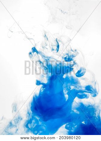 Ink swirl in water isolated on white background. The blue paint in the water. Soft dissemination a droplets of blue ink in water close-up. Abstract vertical photo with soft focus, blurred backdrop.