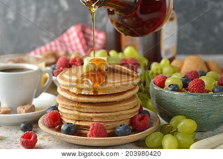 Pancakes with maple syrup and berries on a brown background