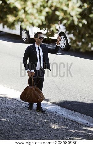 Businessman hailing a cab front sidewalk smiling