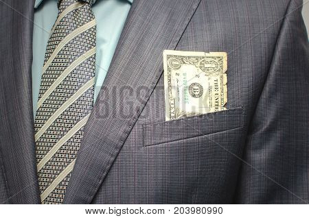 Bribe. Savings. Poverty. Pay the debts. Old worn dollar in the breast pocket of a suit close up.