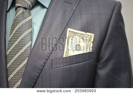 Savings. Poverty. Pay the debts. Old worn dollar in the breast pocket of a suit close up.