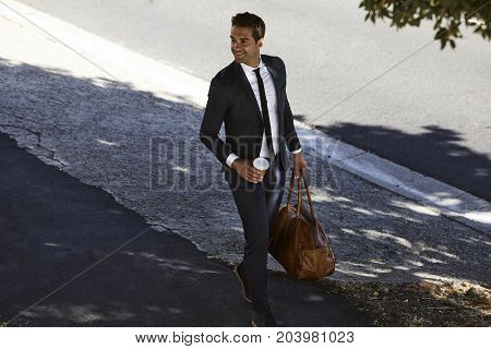 Businessman in suit with bag walking down street smiling