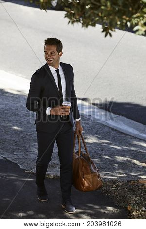 Happy businessman walking with bag and coffee smiling