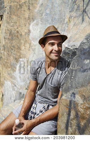 Smiling hiker dude sitting on rocks taking a break