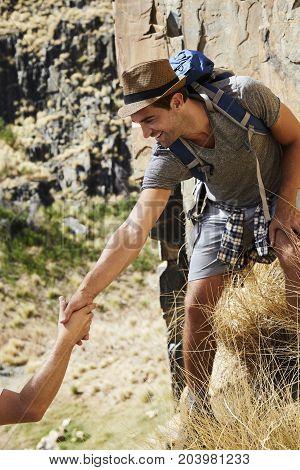 Smiling hiker dude lending hand in climb