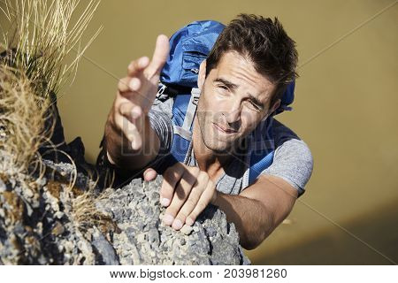 Hiker reaching up for assistance on climb portrait