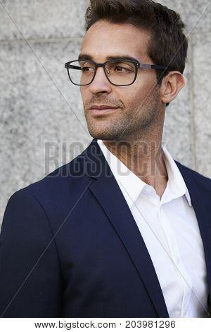 Sharp businessman in suit and glasses smiling