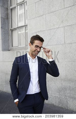 Business dude in spectacles and suit smiling