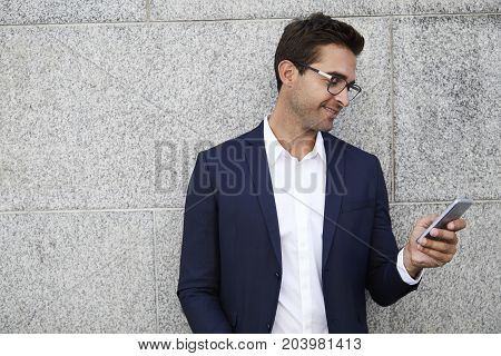 Smart Handsome businessman texting on Smartphone smiling