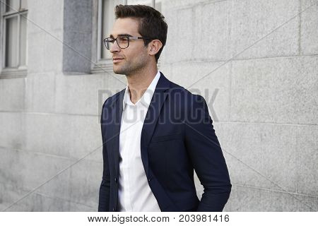 Thoughtful businessman in sharp suit and glasses smiling