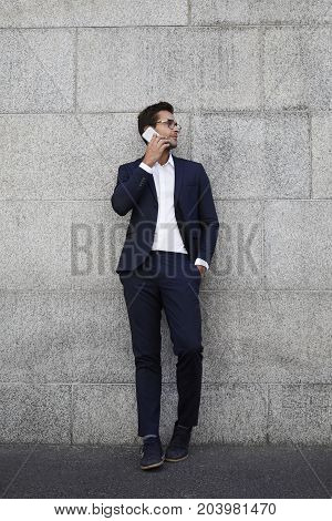 Suited dude leaning against wall on phone looking away