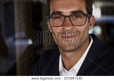 Handsome smiling man in spectacles close up