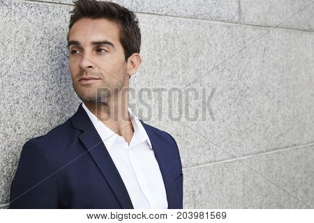 Handsome businessman in suit and shirt looking away
