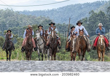 May 27 2017 Sangolqui Ecuador: cowboys arriving on horse back to a rural rodeo in the Andes