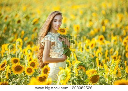 Woman with long hair stands in a field of sunflowers and gets a relaxation.