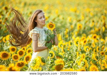 Woman gets a relaxation in a field with yellow sunflowers.
