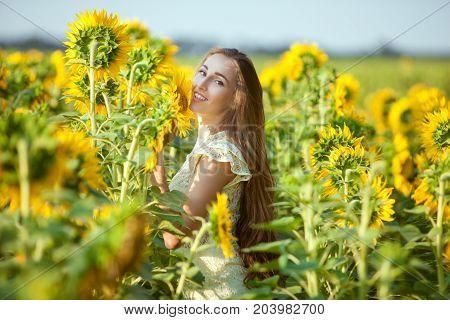 Joyful woman in a field among blooming sunflowers.