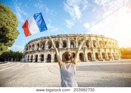 Young woman tourist standing back with french flag in front of the ancient amphitheatre in the old town of Nimes during the sunny morning in France.