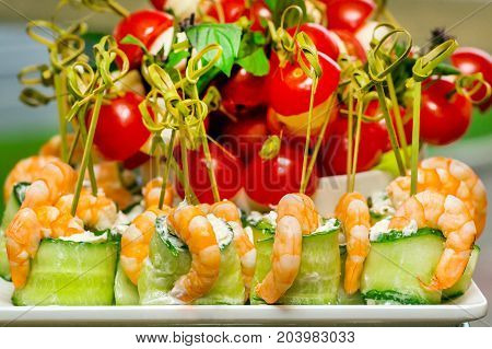 closeup of appetizers with shrimps tomatoes and vegetables with greens