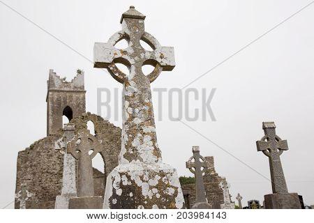 Irish christian graveyard, tomb stones with old church ruin