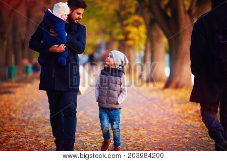 Father With Kids Walking Along The Autumn Street