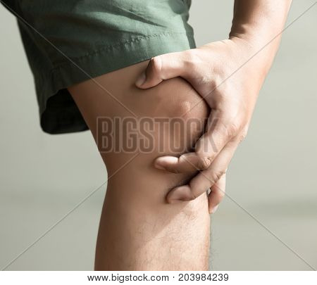 The Knee Man Holds On Suffering From Pain In Knee Closeup. The Lesion Is Highlighted In Red.