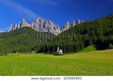 San Giovanni Church in front of dolomites mountain peaks in Santa Magdalena Italy.