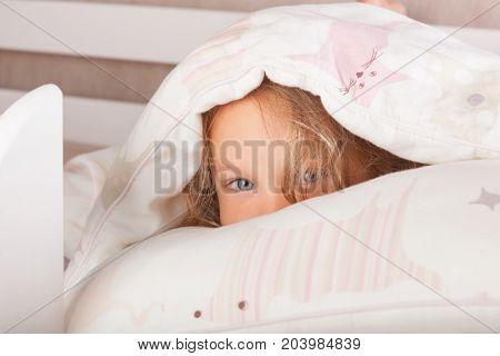 Cute kid Hiding Under The Blanket. Happy morning.