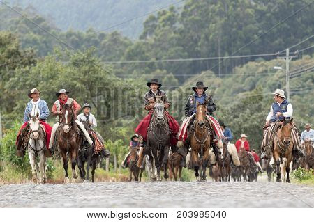 May 27 2017 Sangolqui Ecuador: a large group of local cowboys riding on a country road towards a rural rodeo in the Andes