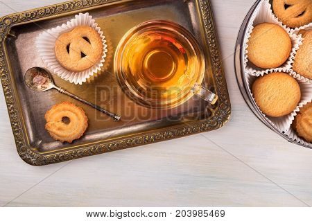 An overhead photo of Danish butter cookies with a cup of tea on a vintage tray, and a tin can, shot from above with a place for text