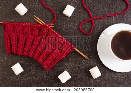 Composition with coffee, red knitting and marsh-mallows on black grunge background.