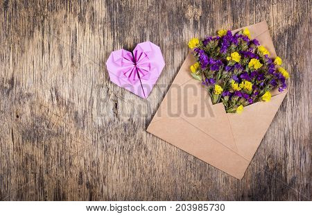 Envelope with flowers. Wildflowers in an envelope. Heart of origami.
