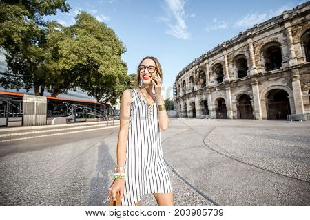 Lifestyle portrait of a young businesswoman walking near old roman amphitheatre in Nimes city, France