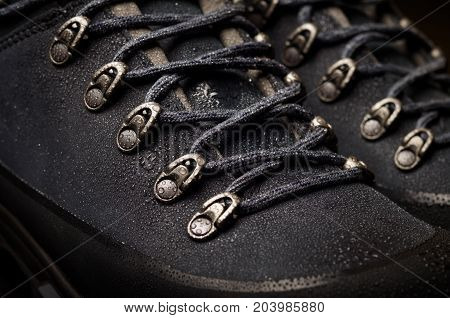Tourist boots for mountain hikes with reinforced soles and membrane material. raindrops on the surface