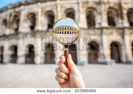 Looking through the magnifying glass on the old roman amphitheatre in Nimes city in France