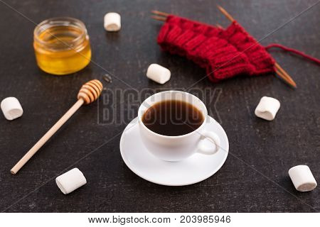 Composition with coffee, honey, red knitting and marsh-mallows on black grunge background.