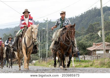 May 27 2017 Sangolqui Ecuador: cowboys from the Andes region on horseback traveling to a rural rodeo on a cobblestone country road