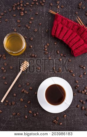 Composition with coffee, honey, red knitting and coffee beans on black background.