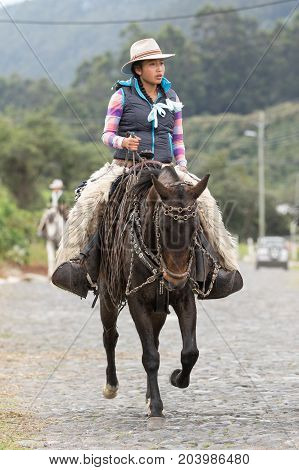 May 27 2017 Sangolqui Ecuador: female cowboy on horse back wearing chaps riding to a rural rodeo in the Andes