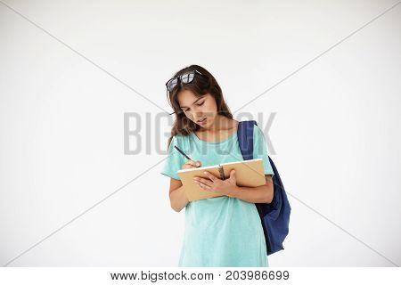 People youth education learning and knowlegde concept. Picture of beautiful college student girl wth glasses on head carrying backpack and writing down in copybook posing isolated in studio