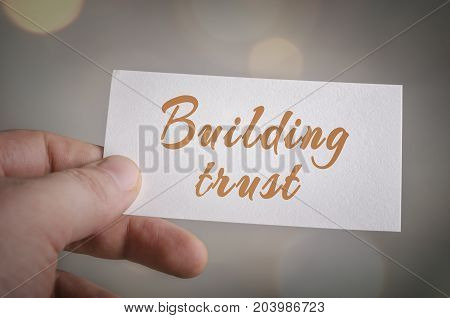 Building trust card in hand with bokeh lights background