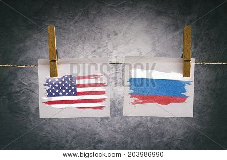 USA and Russian flag painted on paper note attach to rope with clothes pins on dark background
