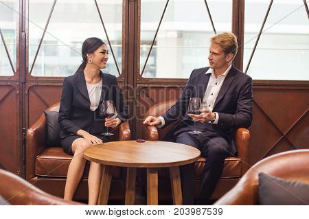 Businessman And Woman Talking For Business While Drinking Red Wine In Bar, People With Business Conc