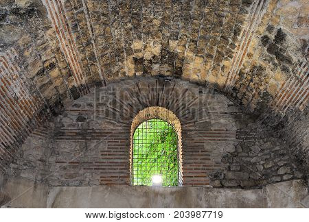 Window with a lattice in an old crypt.