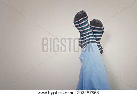 Closeup of a young man`s legs in pajamas with his feet against the wall