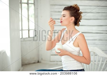 Portrait Of Smiling Woman Tasting Fresh Organic Yogurt sitting in white bright room, wearing in white singlet. Healthy Lifestyle Concept.